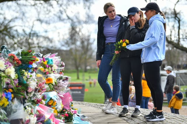 People mourn at a memorial site