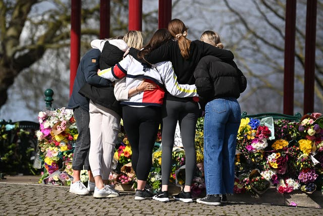 A group of women hug as they stand in front of tributes for Sarah Everard