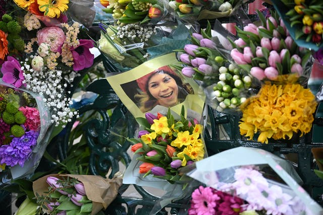 A photograph of Sarah Everard is left with tributes to her at the bandstand on Clapham Common