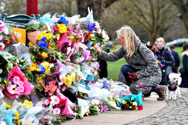 A well-wisher places flowers at a bandstand