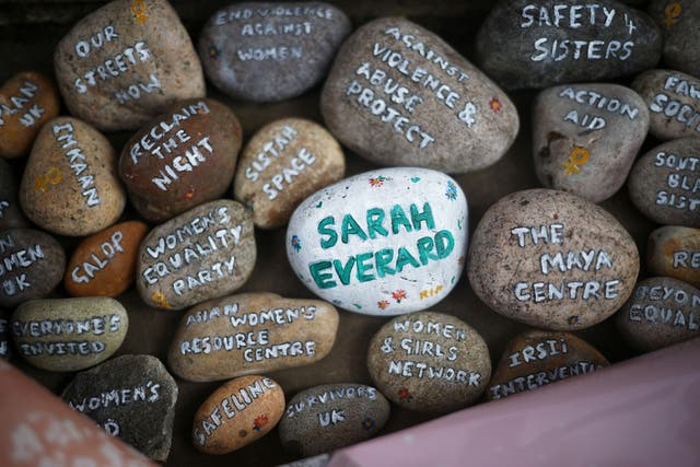 Stones with signatures on them lie at a memorial site at the Clapham Common Bandstand