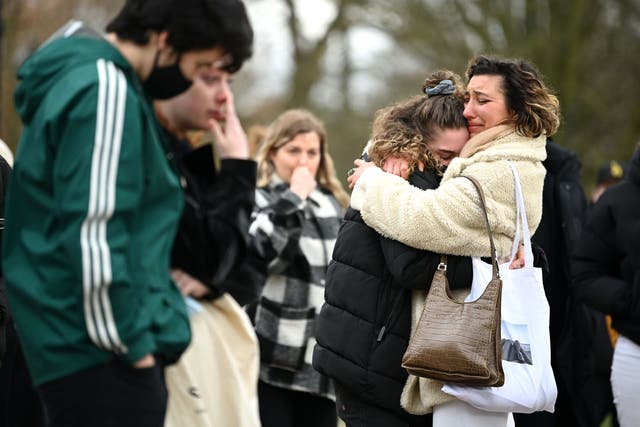 Two women embrace as they stand before tributes for Sarah Everard