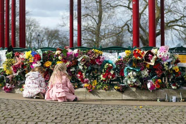 People leave floral tributes