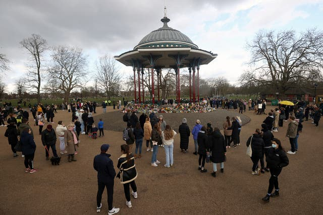People gather at a memorial site in Clapham Common Bandstand