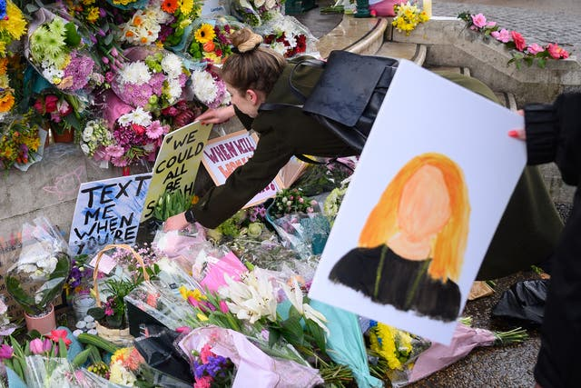 People gather to lay flowers and pay their respects