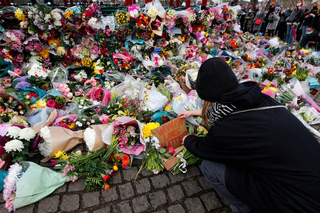 A woman leaves a floral tribute