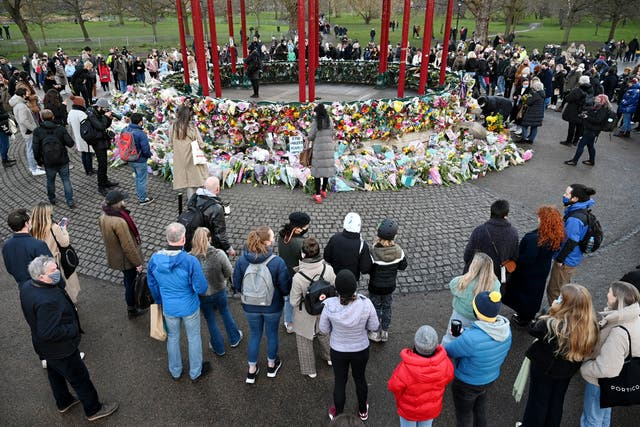 Members of the public surround tributes for Sarah Everard at the bandstand on Clapham Common