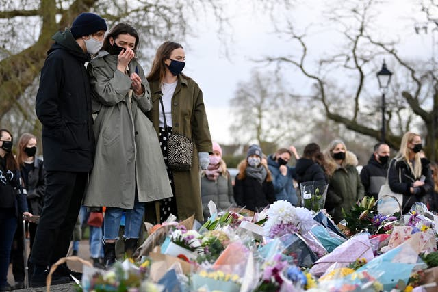 A woman reacts as she looks at tributes