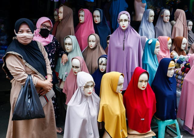Women stand next to hijabs for sale at Tanah Abang textile market in Jakarta, Indonesia