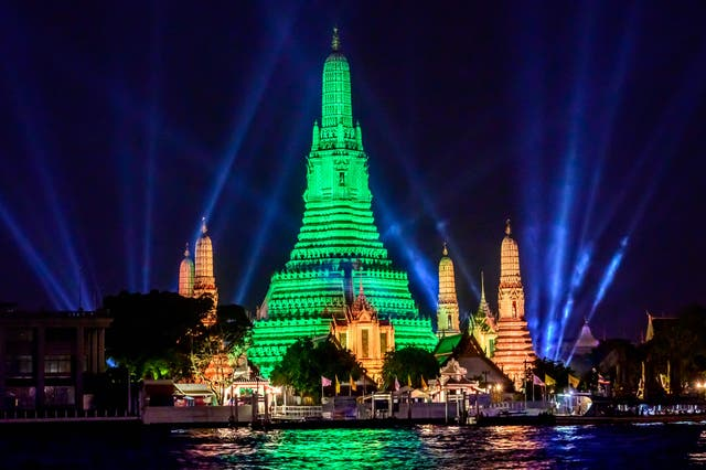 The stupa of the Buddhist temple Wat Arun (Temple of Dawn) is illuminated in green to mark St. Patrick's Day in Bangkok