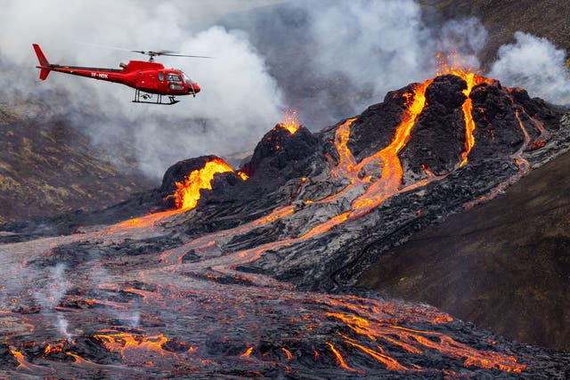 A helicopter flies close to a volcanic eruption which has begun in Fagradalsfjall, Iceland