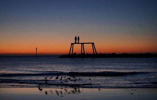"""The sun rises over """"The Couple"""" by artist Sean Henry, which sits off the coast at Newbiggin-by-the-Sea in Northumberland"""