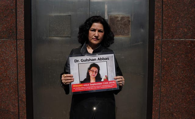 Campaign for Uyghurs Executive Director Rushan Abbas holds a photo of her sister, Gulshan Abbas who is currently imprisoned in a camp during a rally in New York