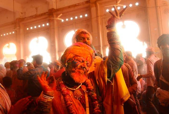 Hindu devotees dance as colored powder is thrown at them at Ladali, or Radha temple, at the legendary hometown of Radha, consort of Hindu God Krishna, during Lathmar holi, in Barsana, India