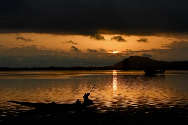 A man rows a boat against the setting sun at the Dal Lake after a downpour in Srinagar