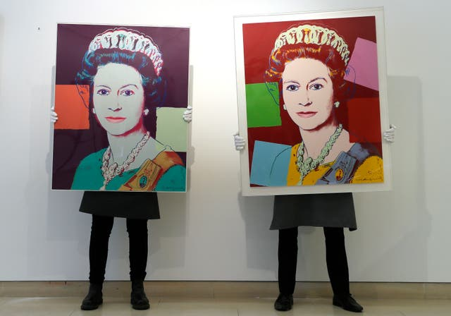 Gallery technicians display Andy Warhol screenprints Queen Elizabeth II, from: Reigning Queens screenprint in colours, 1985, left, and Queen Elizabeth II, from: Reigning Queens (Royal Edition) screenprint in colours with diamond dust, 1985, right, at Christie's auction rooms in London