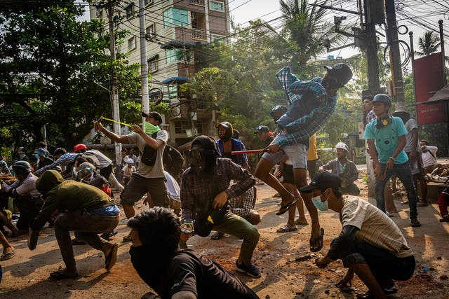 Anti-coup protesters use slingshots and pelt stones towards approaching security forces on March 28, 2021 in Yangon, Myanmar. Myanmar's military Junta continued a brutal crackdown on a nationwide civil disobedience movement in which thousands of people have turned out in continued defiance of live ammunition.