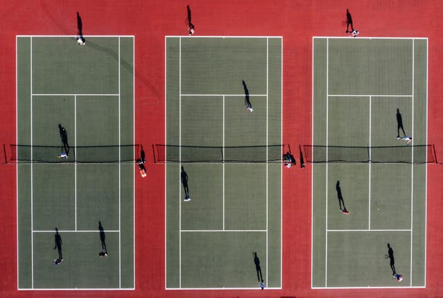 An aerial photo shows people playing tennis at the Mersey Bowman Lawn Tennis Club in Liverpool northwest England on March 29, 2021, as England's third Covid-19 lockdown restrictions ease, allowing groups of up to six people to meet outside. - People in England rushed outside Monday to enjoy sports, picnics and other previously prohibited activities, as the nation entered the second phase of its coronavirus lockdown easing thanks in large part to a successful vaccination drive