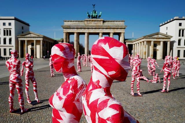 "Mannequins wrapped in barrier tape stand in front of Berlin's landmark Brandenburg Gate as part of German artist Dennis Josef Meseg's Corona Memorial called ""It is Like it is"""