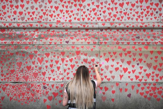 A woman adds a heart to the National Covid Memorial Wall in London