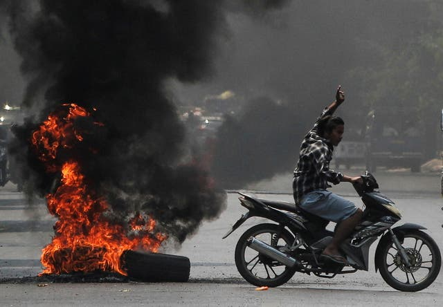 Man flashes three-finger salute next to burning tires during a protest against the military c