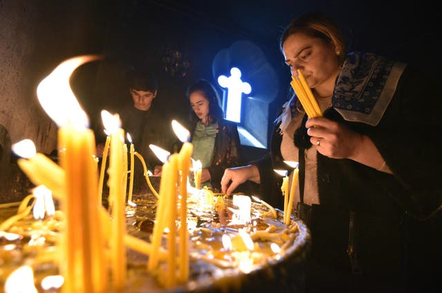 Christian worshippers light candles during an Easter service in Yerevan, the Armenian capital