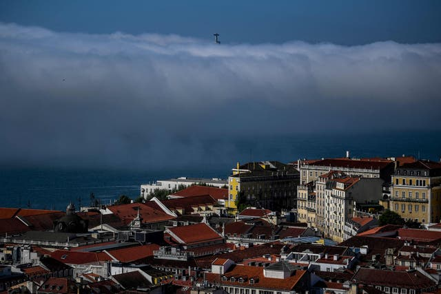 The Statue of Christ appears behind clouds from the Sao Jorge Castle in Lisbon as the Portuguese government eased coronavirus restrictions