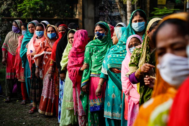 Voters stand in queue to cast their votes at a polling booth during third phase of West Bengal state elections in Baruipur, South 24 Pargana district, India