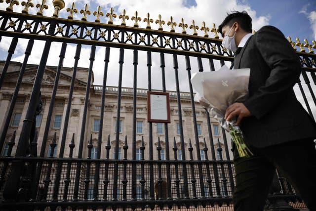 A man arrives to lay a bunch of flowers outside Buckingham Palace in central London after the announcement of the death of Britain's Prince Philip, Duke of Edinburgh. - Queen Elizabeth II's husband Prince Philip, who recently spent more than a month in hospital and underwent a heart procedure, died on April 9, Buckingham Palace announced. He was 99.