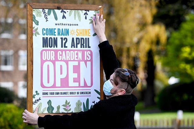 A pub staff pins up a sign announcing the reopening of the Fox on the Hill pub on Denmark Hill in London