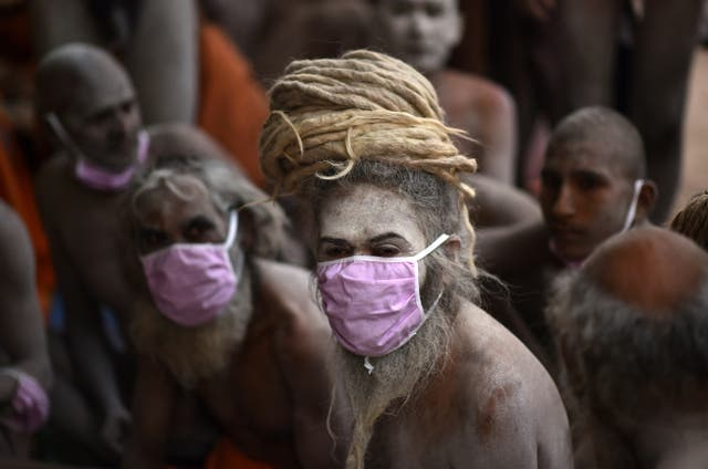 An Indian holi man during the Kumbh Mela royal bath (Sacred Hindu Pilgrimage) in Haridwar, Uttarakhand, India. Thousands of pilgrims are gathering and taking holy dip in Kumbh Mela that is a mass Hindu pilgrimage which occurs after every twelve years and rotates among four locations