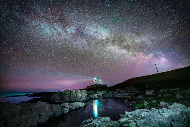 The core of the Milky Way becomes visible in the early hours of Tuesday morning as it moves over Bamburgh Lighthouse at stag Rock in Northumberland