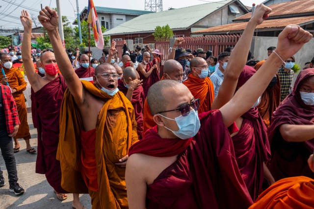 This photo taken and received courtesy of an anonymous source shows Buddhist monks gesturing while taking part in a demonstration with protesters against the military coup in Mandalay during the Myanmar New Year festival of Thingyan