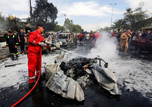 A firefighter inspects the site of a car bomb attack in Sadr City district of Baghdad, Iraq
