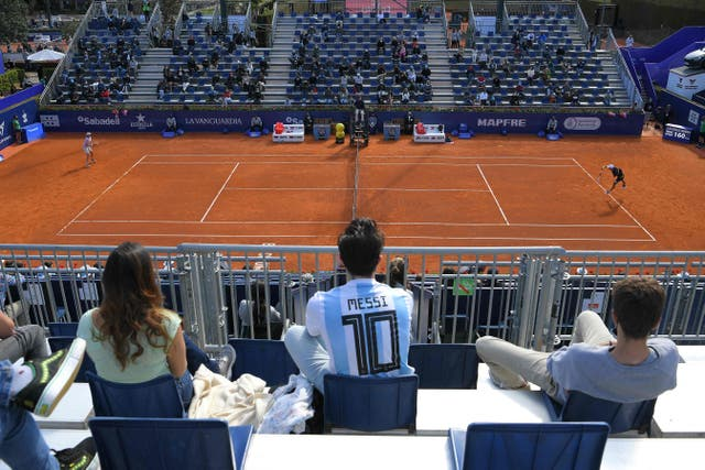 A spectator wearing a football jersey of Argentina's forward Lionel Messi attends the ATP Barcelona Open tennis tournament singles match between Japan's Kei Nishikori and Argentina's Guido Pella at the Real Club de Tenis in Barcelona