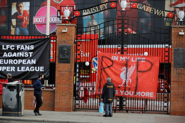 People stand in front of anti Super League banners outside Anfield as twelve of Europe's top football clubs, including Liverpool, launch a breakaway league