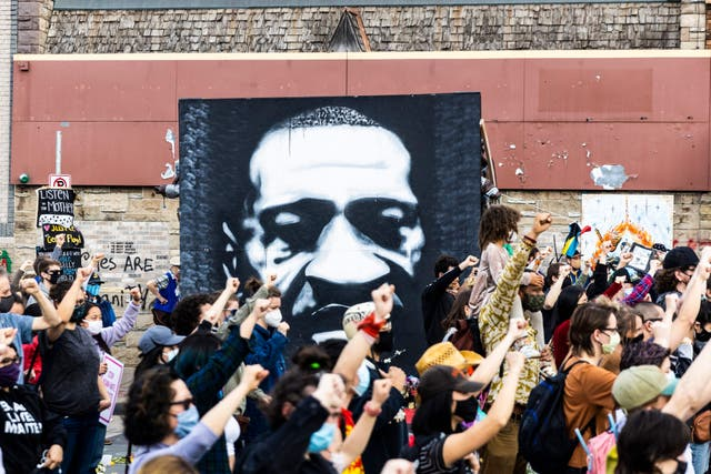 People raise their fist during a demonstration near the George Floyd Memorial in Minneapolis, Minnesota