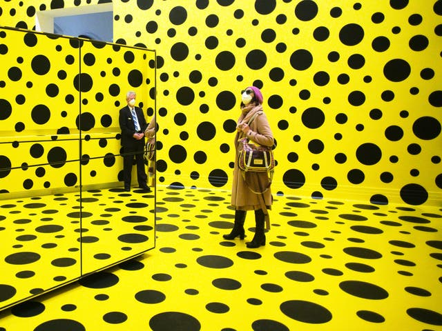 People walk through the art work 'THE SPIRITS OF THE PUMPKINS DESCENDED INTO THE HEAVENS' by Yayoi Kusama, during the press preview of a retrospective exhibition of the Japanese artist at the Martin Gropius Bau museum in Berlin, Germany
