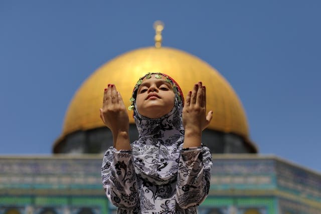 A girl prays in front of the Dome of the Rock, in the compound known to Muslims as Noble Sanctuary and to Jews as Temple Mount, in Jerusalem's Old City, on the second Friday of the holy month of Ramadan, as coronavirus restrictions ease around the country, in Jerusalem