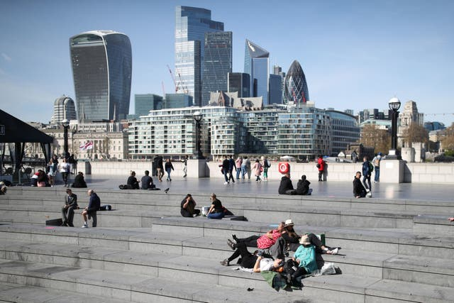 People enjoy the warm weather at City Hall near Tower Bridge in central London