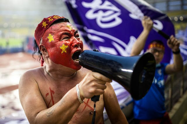 Fans of Wuhan Three Towns FC cheer for their team during the 1st round match Wuhan Three Towns FC and Beijing Institute of Technology FC during Chinese Football  League One in Wuhan, China