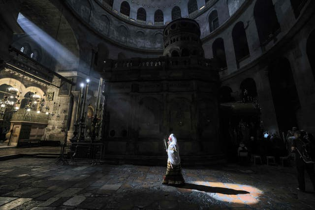 An Ethiopian Orthodox Christian worshipper walks around the Edicule, the place believed to be where Jesus Christ was buried, during Palm Sunday celebrations at the Church of the Holy Sepulchre in Jerusalem