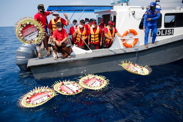Balinese people lay wreaths with names of the crew on board the sunk Indonesian Navy submarine KRI Nanggala during a prayer at the sea near Labuhan Lalang, Bali, Indonesia