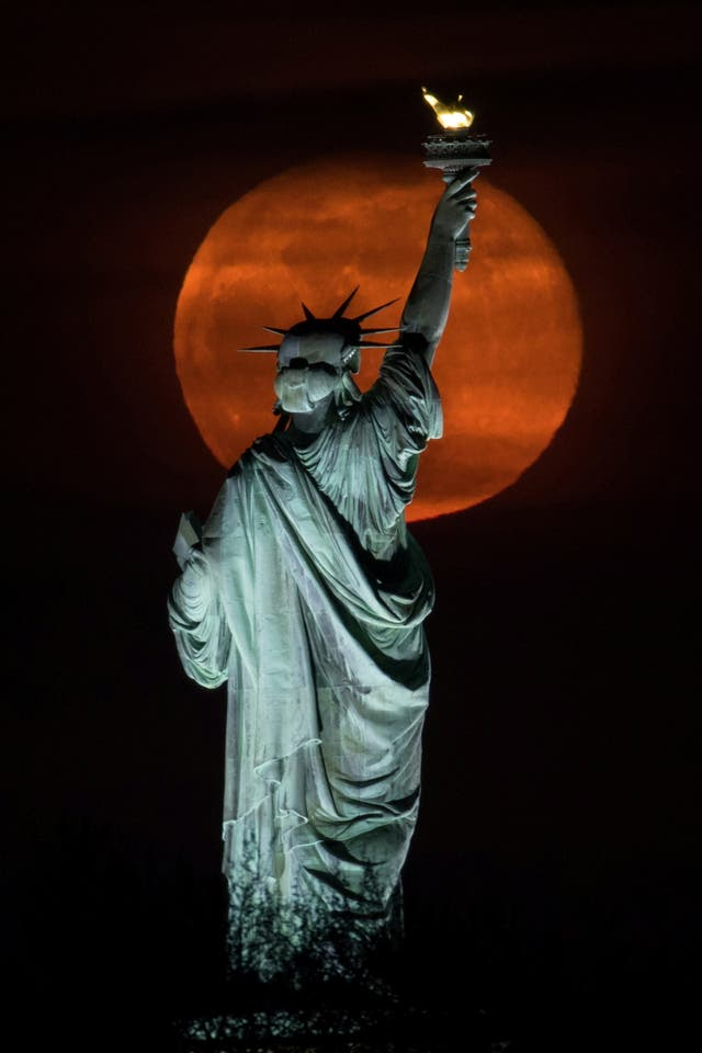 The full moon, known as the Super Pink Moon rises behind the Statue of Liberty in New York City,