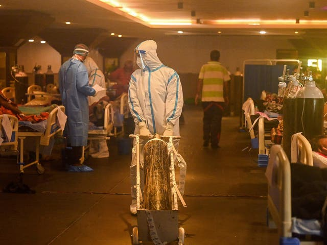 Health workers wearing PPE attends to coronavirus patients inside a banquet hall temporarily converted into a covid care centre in New Delhi