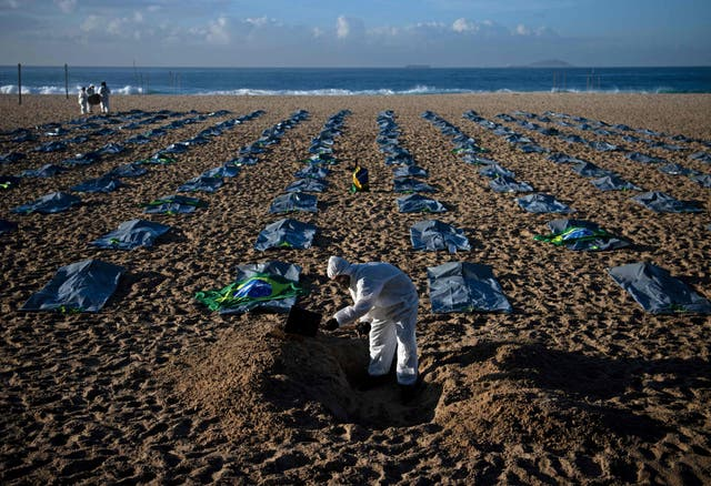 A demonstrator from the Rio de Paz human rights activist group digs a symbolic grave in front of rows of bags symbolising bodybags on Copacabana beach, during a protest against the Brazilian governments handling of the coronavirus pandemic, in Rio de Janeiro