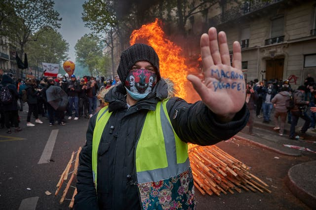 A Gilet Jaune, or yellow vest, protestor stands in front of a burning barricade holding his hand up with an inscription calling for President Macron to resign as May Day Protest turn violent near Place de la Republique in Paris, France