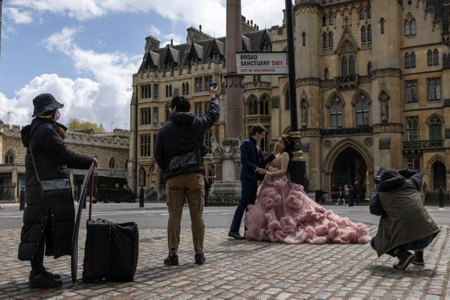 A couple have wedding photos taken in Westminster, London