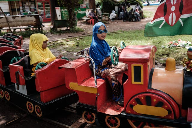 Muslim girls ride on a mini train after attending the Eid Al-Fitr prayer that marks the end of the Holy month of Ramadan at Uhuru Park in Nairobi, Kenya