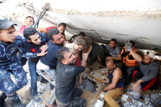 Rescuers carry Suzy Eshkuntana, 6, as they pull her from the rubble of a building at the site of Israeli air strikes, in Gaza City
